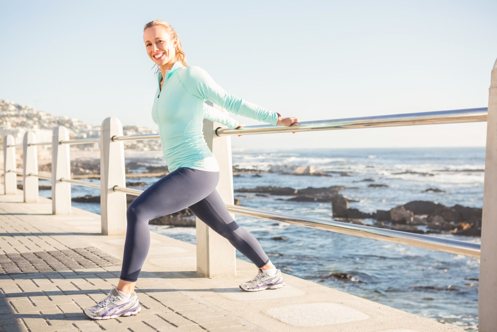 Portrait of smiling fit blonde stretching on railing at promenade